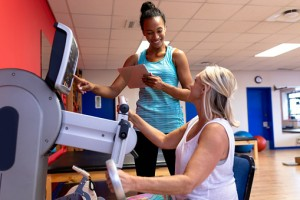 Trainer assisting disabled active senior woman to exercise in exercise equipment